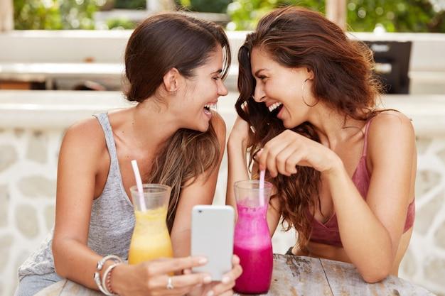 Casal de lésbicas femininas felizes lêem boas notícias no celular ou faz videochamada, sente-se em um café moderno