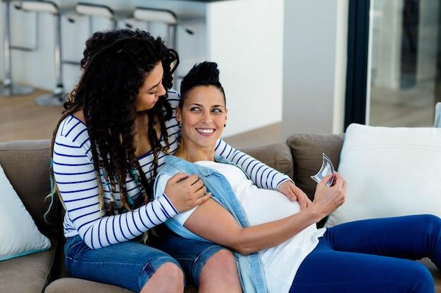 Casal de lésbicas grávidas sentado no sofá e olhando para o relatório de ecografia