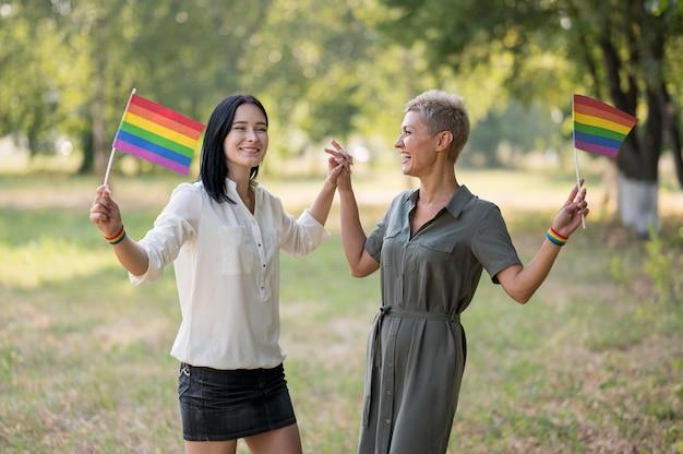 Casal de lésbicas no parque com bandeiras