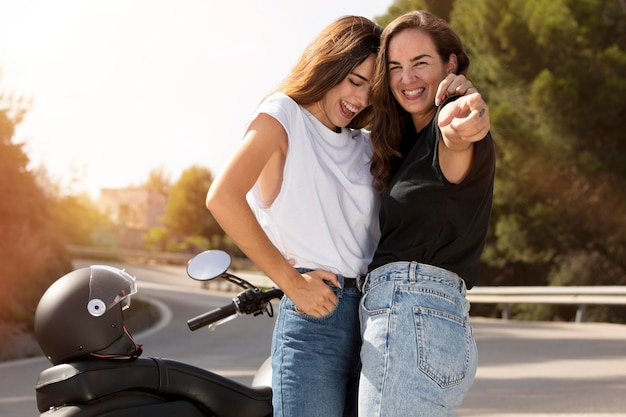 Casal de lésbicas se abraçando perto de uma motocicleta durante uma viagem