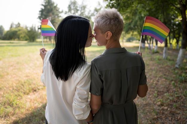 Casal de lésbicas se beijando enquanto segura a bandeira