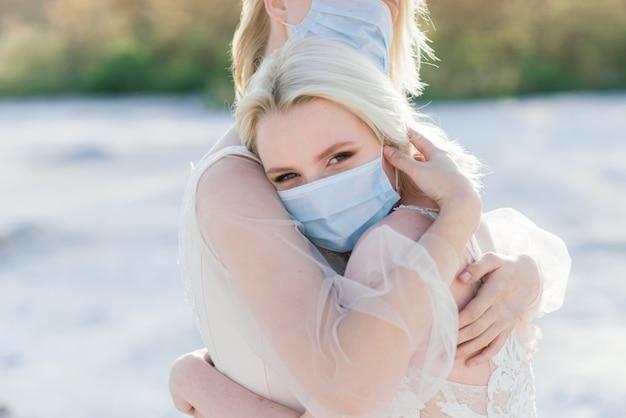 Casal de lésbicas se casando na areia usando máscaras