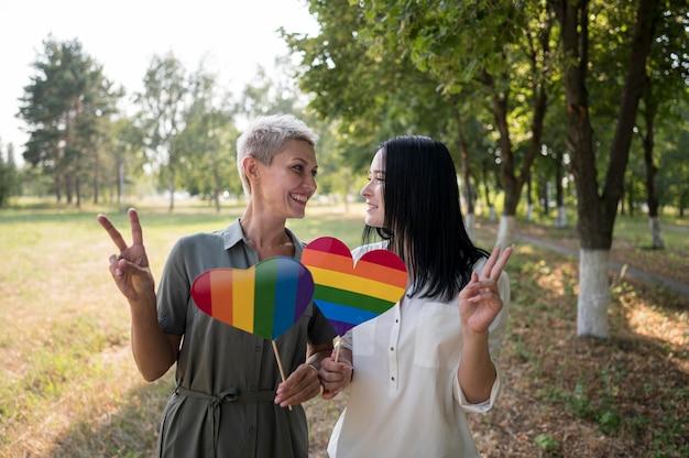 Casal de lésbicas segurando bandeira lgbt em formato de coração