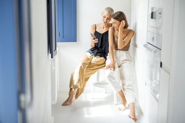 Casal de lésbicas sentados juntos e se divertir olhando no celular enquanto está sentado no interior da casa moderna e branca. conceito de relações homossexuais e estilo de vida digital em casa