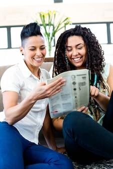 Casal de lésbicas sorrindo enquanto lê o jornal