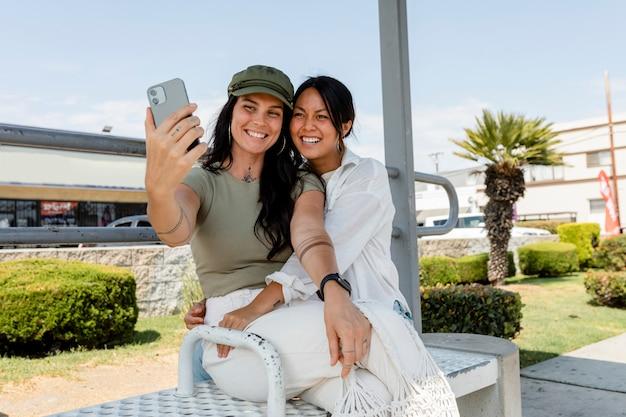 Casal de lésbicas tirando selfies em um encontro