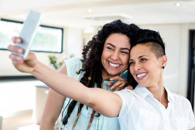 Casal de lésbicas tomando uma selfie no telefone na sala de estar