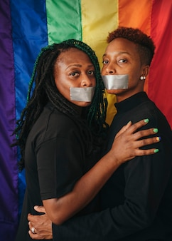 Casal de lésbicas usando fitas na boca contra uma bandeira de arco-íris