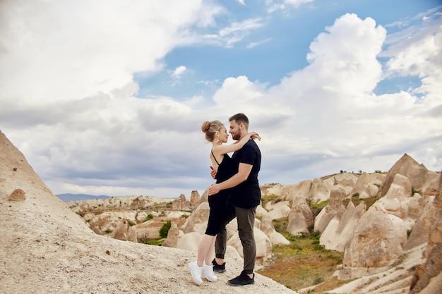 Casal de leste de moda abraçando-se com a montanha. relacionamento amoroso de homem e mulher