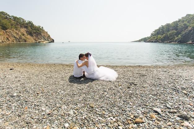 Casal de lua de mel viaja mar e resort de praia na europa. noiva e noivo