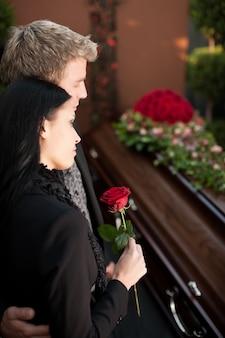 Casal de luto no funeral com caixão
