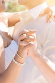 Casal de mãos dadas, close-up. dia do casamento.