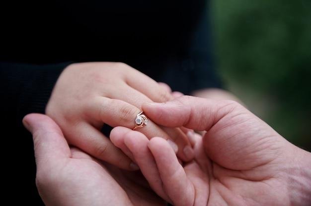 Casal de mãos dadas com anel de diamante