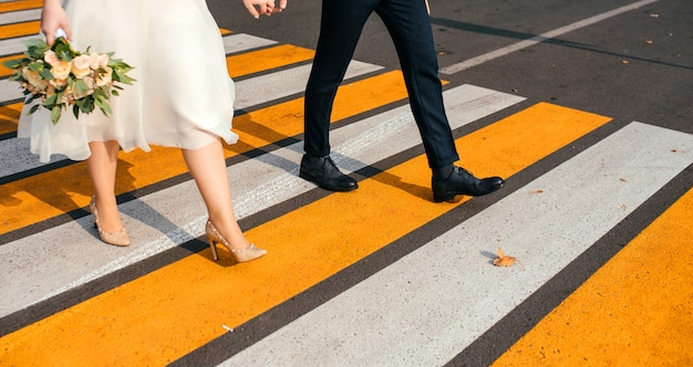 Casal de mãos dadas cruzando o cruzamento da cidade