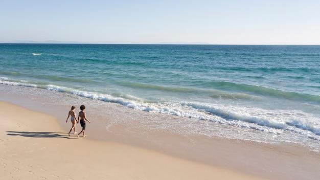 Casal de mãos dadas e indo para o mar