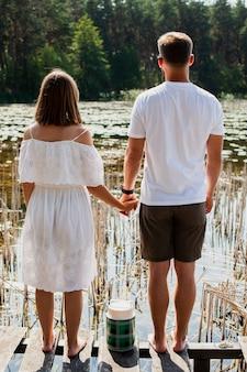 Casal de mãos dadas e olhando um ao outro por trás