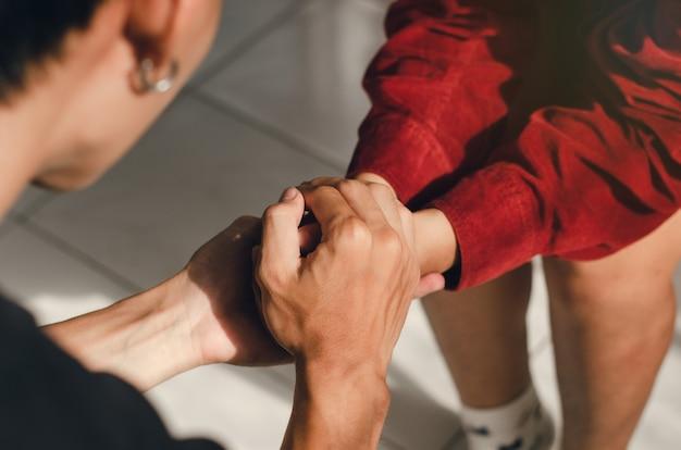 Casal de mãos dadas e orando juntos com humildade no amor de deus