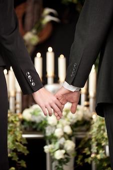 Casal de mãos dadas em um funeral