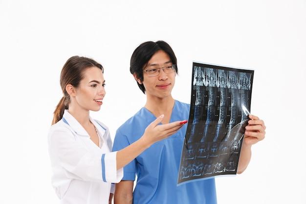 Casal de médicos confiantes vestindo uniforme em pé, isolado sobre uma parede branca, examinando uma fotografia de raio-x