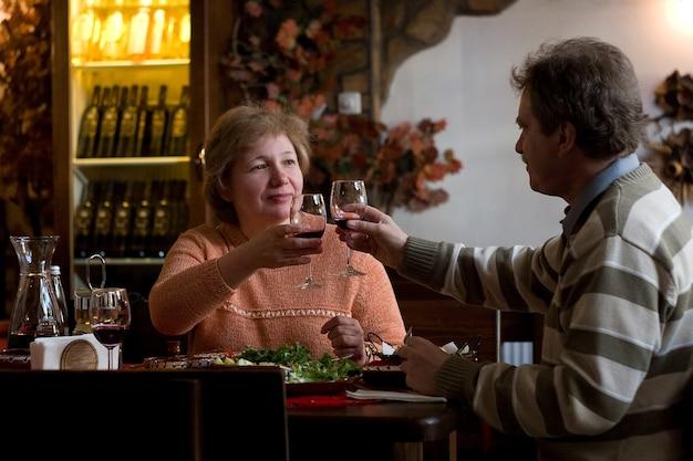 Casal de meia idade bebendo vinho. família está fazendo atividades de lazer e curtindo no restaurante