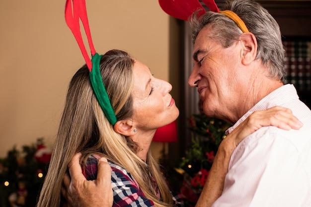 Casal de meia idade com chifres de rena se beijando