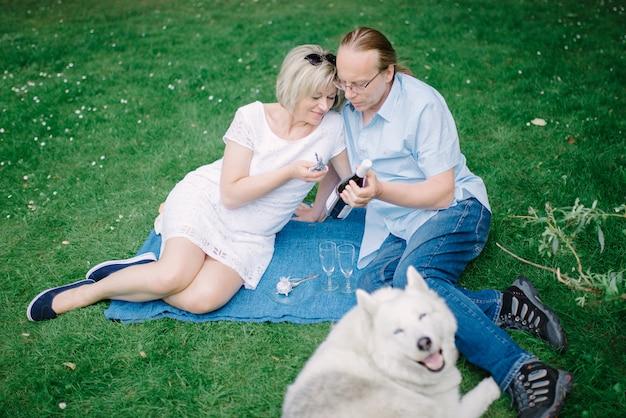 Casal de meia idade com seu animal de estimação no piquenique