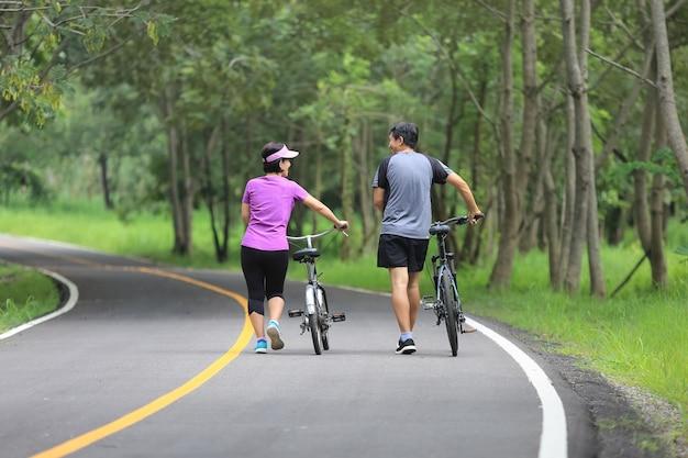 Casal de meia-idade fazendo exercícios relaxantes com bicicleta no parque