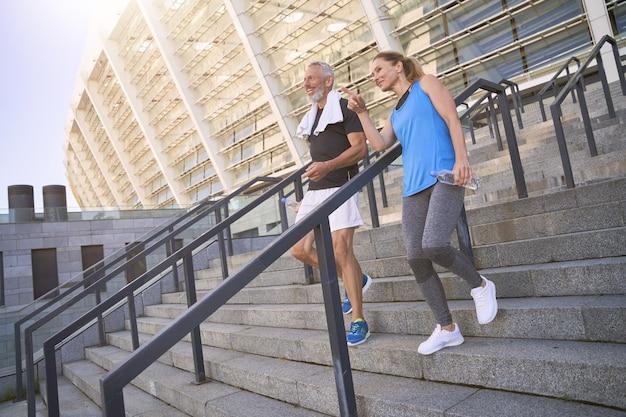 Casal de meia idade, homem e mulher em roupas esportivas, descendo as escadas após se exercitarem juntos