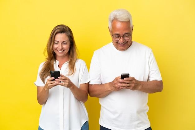 Casal de meia-idade isolado em fundo amarelo surpreso e mandando mensagem ou e-mail com o celular