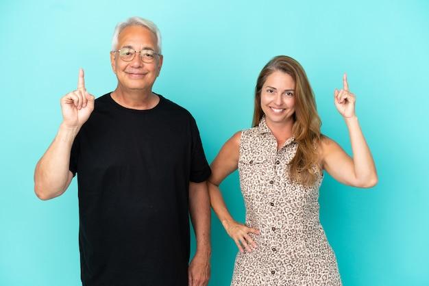 Casal de meia-idade isolado em fundo azul, mostrando e levantando um dedo em sinal dos melhores