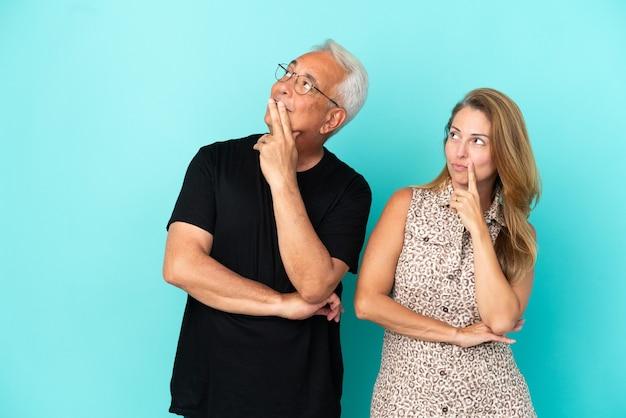 Casal de meia-idade isolado em um fundo azul pensando em uma ideia enquanto olha para cima