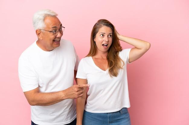 Casal de meia-idade isolado em um fundo rosa apontando o dedo para o lado com uma cara surpresa