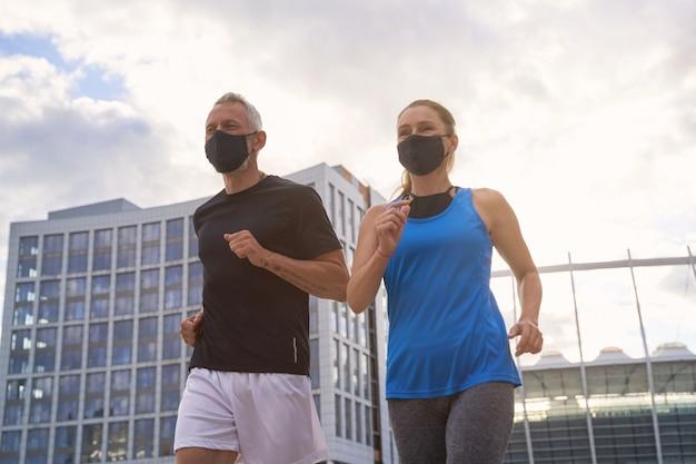 Casal de meia-idade motivado com máscaras protetoras, correndo juntos em ambiente urbano no
