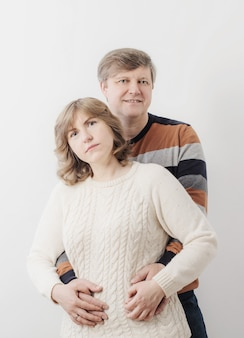 Casal de meia idade no fundo da parede branca