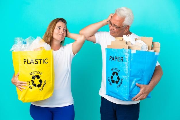 Casal de meia-idade segurando um saco de reciclagem cheio de papel e plástico isolado no fundo branco, tendo dúvidas enquanto coça a cabeça
