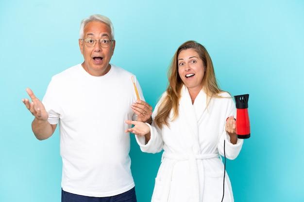 Casal de meia-idade segurando um secador e uma escova de dentes isolados em um fundo azul com expressão facial surpresa e chocada
