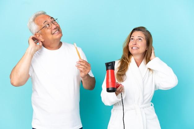 Casal de meia-idade segurando um secador e uma escova de dentes isolados em um fundo azul, pensando uma ideia enquanto coça a cabeça