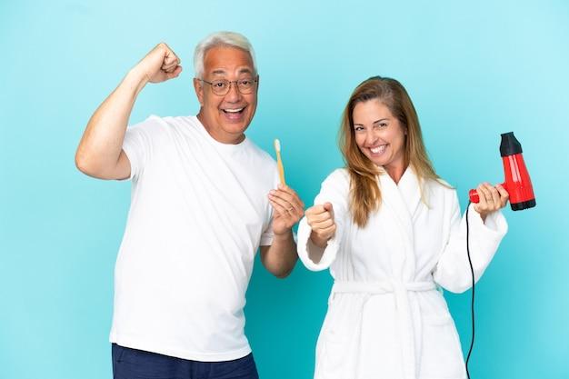 Casal de meia-idade segurando um secador e uma escova de dentes isolados no fundo azul e comemorando a vitória na posição de vencedor