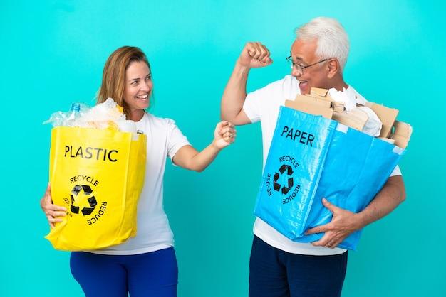 Casal de meia-idade segurando uma sacola de reciclagem cheia de papel e plástico, isolada no fundo branco, comemorando a vitória na posição de vencedora