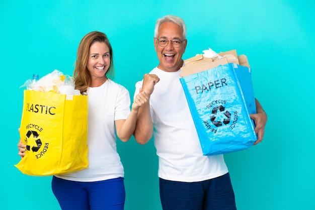 Casal de meia-idade segurando uma sacola de reciclagem cheia de papel e plástico, isolada no fundo branco, comemorando uma vitória