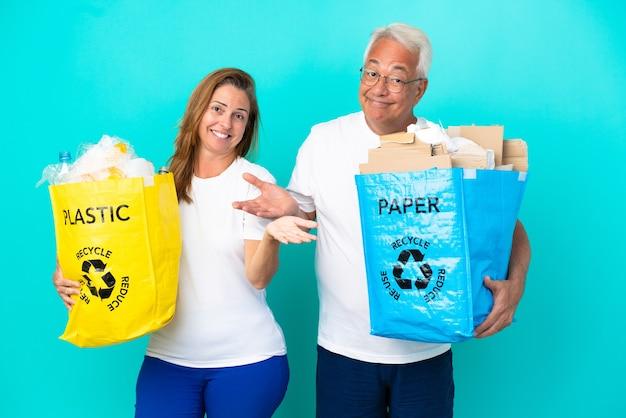 Casal de meia-idade segurando uma sacola de reciclagem cheia de papel e plástico isolado no fundo branco, tendo dúvidas enquanto levanta as mãos e os ombros