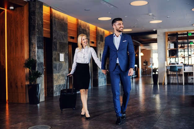 Casal de meia-idade sorridente, de mãos dadas e andando no saguão de um hotel chique. eles vão para o quarto. a mulher está puxando uma mala.