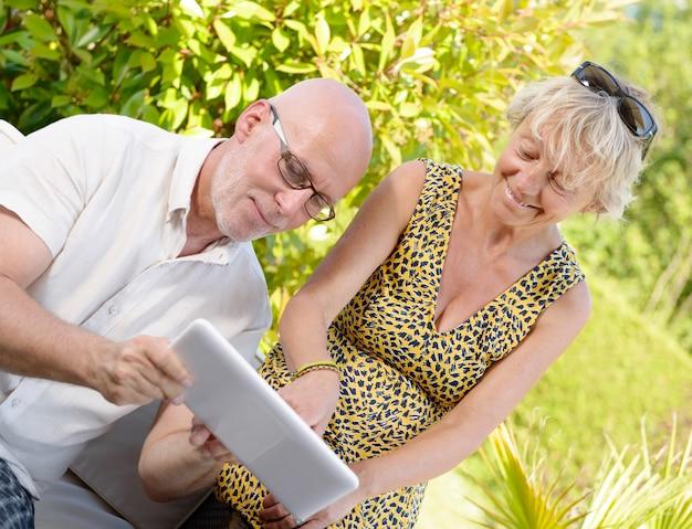 Casal de meia idade, sorrindo, usando um tablet em seu jardim