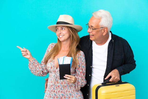 Casal de meia-idade vai viajar e segurando uma mala isolada em um fundo azul apresentando uma ideia enquanto olha sorrindo para