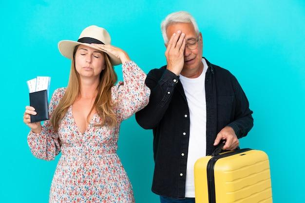 Casal de meia-idade vai viajar e segurando uma mala isolada em um fundo azul com expressão facial surpresa e chocada