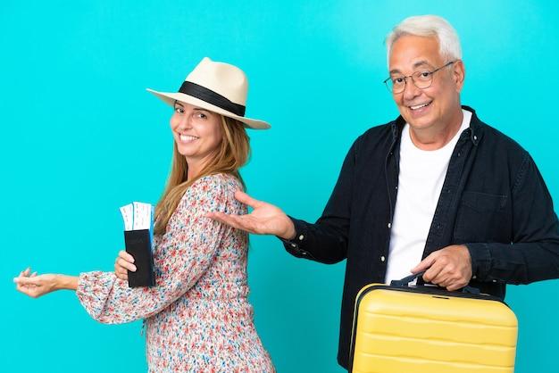Casal de meia-idade vai viajar e segurando uma mala isolada em um fundo azul estendendo as mãos para o lado para convidar para vir