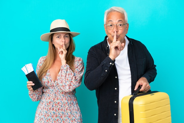 Casal de meia-idade vai viajar e segurando uma mala isolada em um fundo azul, mostrando sinal de silêncio, gesto colocando o dedo na boca