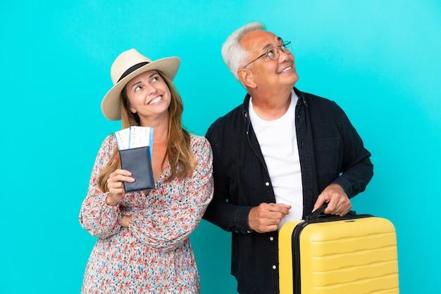 Casal de meia-idade vai viajar e segurando uma mala isolada em um fundo azul, olhando para cima enquanto sorri