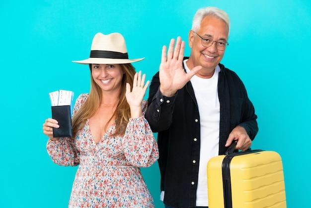 Casal de meia-idade vai viajar e segurando uma mala isolada em um fundo azul, saudando com a mão com expressão feliz