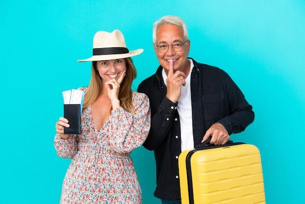 Casal de meia-idade vai viajar e segurando uma mala isolada em um fundo azul, sorrindo com uma expressão doce